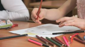 Little girl draws the pictures using color pencils stock footage