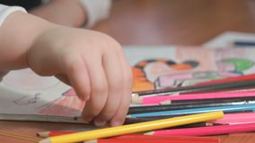 Little girl draws the pictures using color pencils stock video footage