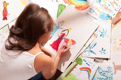 Little girl draws a princess. Little girl draws among her drawings stock photography