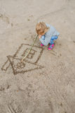 Little girl draws in the sand Stock Images
