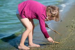 Little girl draws on the sand Stock Photography