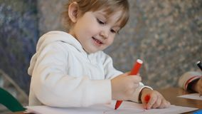 A little girl draws on a sheet of red marker circle.  stock video