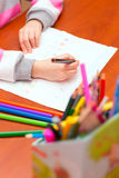 Little girl draws sitting at table. Stock Image