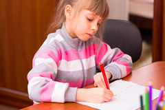 Little girl draws sitting at table. Royalty Free Stock Photography