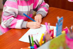 Little girl draws sitting at table. Stock Photography