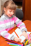 Little girl draws sitting at table. Royalty Free Stock Images