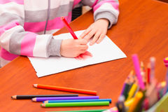Little girl draws sitting at table. Stock Photo