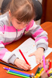Little girl draws sitting at table. Stock Photos