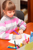 Little girl draws sitting at table. Royalty Free Stock Photo