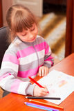Little girl draws sitting at table. Stock Images