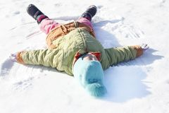 . little girl draws on the snow angel. shallow depth of field stock photo