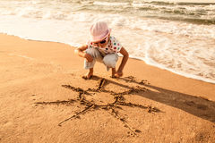 Little girl draws  sun on sand at the beach Stock Photography