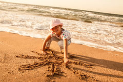 Little girl draws  sun on sand at the beach Royalty Free Stock Photos