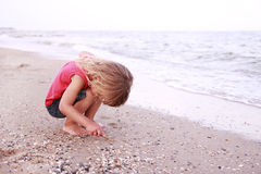 Little girl draws a sun in the sand on the seashore Royalty Free Stock Images
