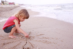Little girl draws a sun in the sand on the seashore Stock Image