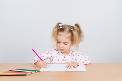 Little girl draws at table pencils. Stock Photo