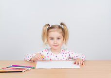 Little girl draws at table pencils. Stock Image