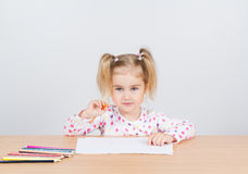 Little girl draws at table pencils. Stock Photos