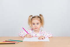 Little girl draws at table pencils. Stock Images