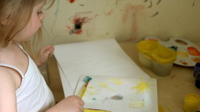 Little girl draws using a brush on a piece of paper. stock video footage