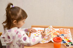 The little girl draws water color paints.  stock image