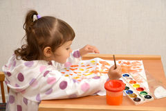 The little girl draws water color paints.  stock photos
