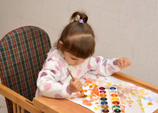 The little girl draws water color paints.  stock photo