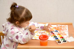 The little girl draws water color paints.  royalty free stock photos