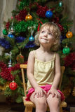 Little girl dreamily looking up on chair near Christmas tree Stock Image