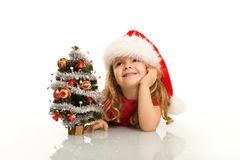 Little girl dreaming about christmas. Little girl with santa hat dreaming about christmas - isolated