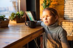 Little girl dreaming with a cup of tea stock photo