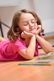 Little girl dreaming while reading a book Stock Photography