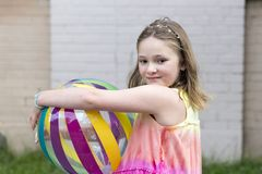 Little girl with dreamy look holding multicolored beach ball stock photo