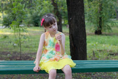 Little girl in dress on bench with ice cream Stock Photography