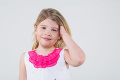 A little girl in a dress with butterflies corrects blond hair Stock Photography