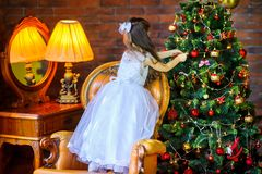 Girl decorate a festive Christmas tree. Little girl in a dress decorates with balls festive Christmas tree Royalty Free Stock Images