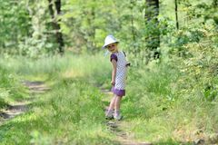 Little girl in a dress and hat on a walk in forest Royalty Free Stock Photography