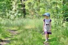 Little girl in a dress and hat on a walk in forest Stock Images