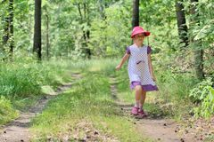 Little girl in a dress and hat on a walk in forest Royalty Free Stock Image