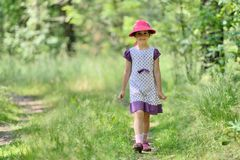 Little girl in a dress and hat on a walk in forest Stock Image