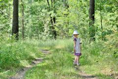 Little girl in a dress and hat on a walk in forest Stock Photo