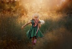 Little girl in dress and hat walking in a green field