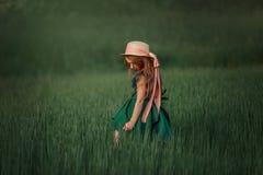 Little girl in dress and hat walking in a green field