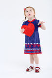 Little girl in dress holds red heart and looks up Stock Images