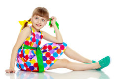 A little girl in a dress with a pattern from multi-colored circl Royalty Free Stock Photo