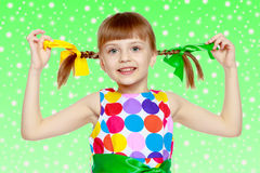 A little girl in a dress with a pattern from multi-colored circl Royalty Free Stock Photography