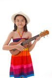 Little girl in dress playing the ukulele royalty free stock photography
