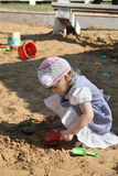Little girl in dress plays in sandbox Royalty Free Stock Image