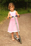 Little girl in dress rides scooter on nature Royalty Free Stock Image
