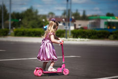 Little girl in dress riding her scooter on the park. Summertime Royalty Free Stock Photography